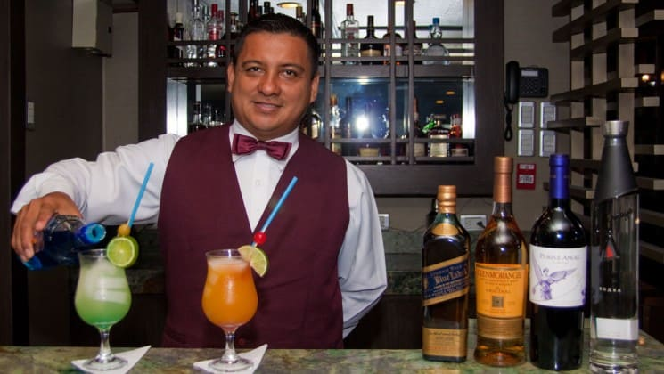 Bartender making two tropical drinks at well-stocked bar aboard Sea Star Journey luxury yacht Galapagos cruise
