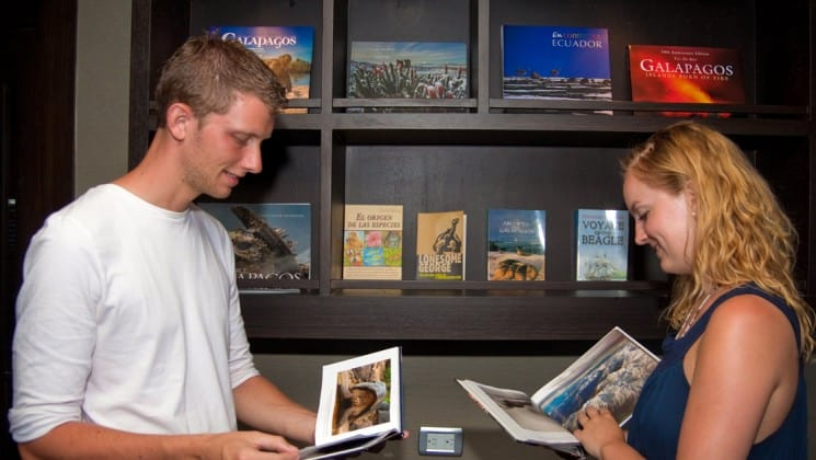Man and woman browse books in library aboard Sea Star Journey yacht in the Galapagos Islands