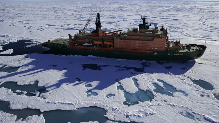 50 Years of Victory anchored next to the ice shelf with people walking in front of the bow in Antarctica.
