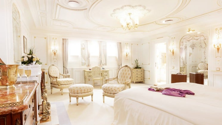 pristine white room with a large bed and ottomans aboard the Lindblad Sea Cloud luxury mediterranean small ship