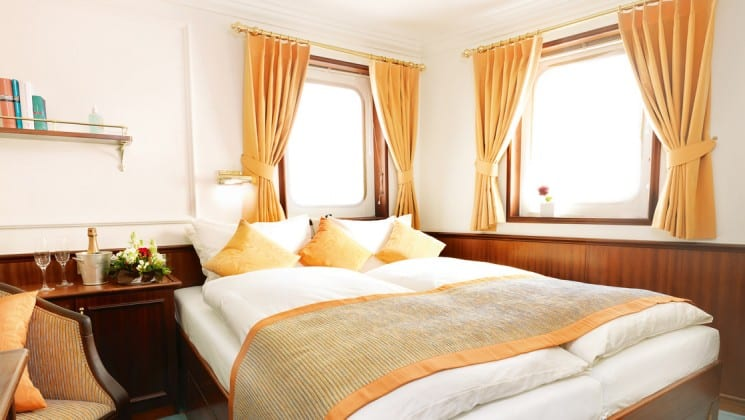 cabin with large bed, 2 large windows, a table and chair on the Lindblad Sea Cloud mediterranean luxury yacht