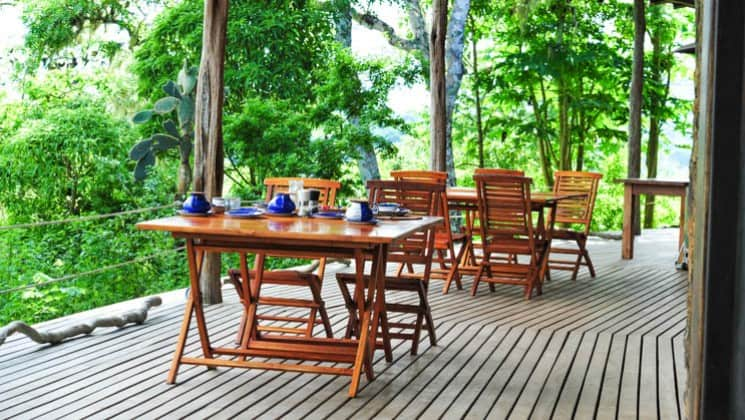 Dining tables set up on the outdoor deck with jungle views at Galapagos Safari Camp Santa Cruz Highlands in the Galapagos Islands