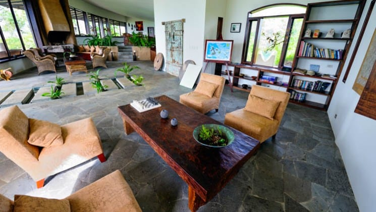 Lodge interior with coffee tables, chairs, book cases and plants at Galapagos Safari Camp Santa Cruz Highlands in the Galapagos Islands
