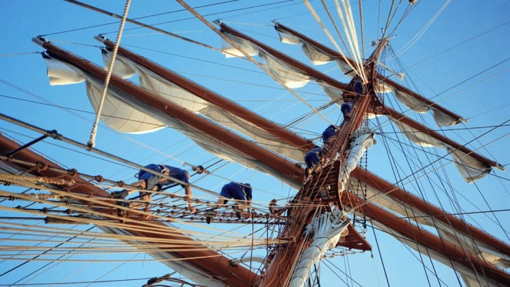 looking up at the Sea Cloud luxury mediterranean yacht mast with crew members climbing it