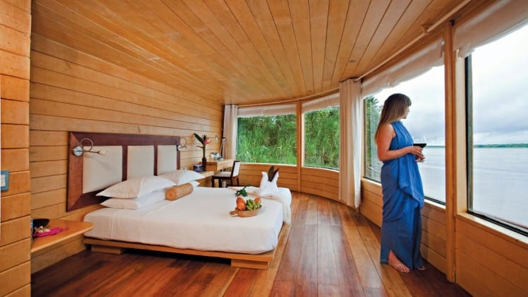 Woman standing in Master Suite with large bed and 180-degree picture windows aboard Delfin II riverboat on Amazon River cruise