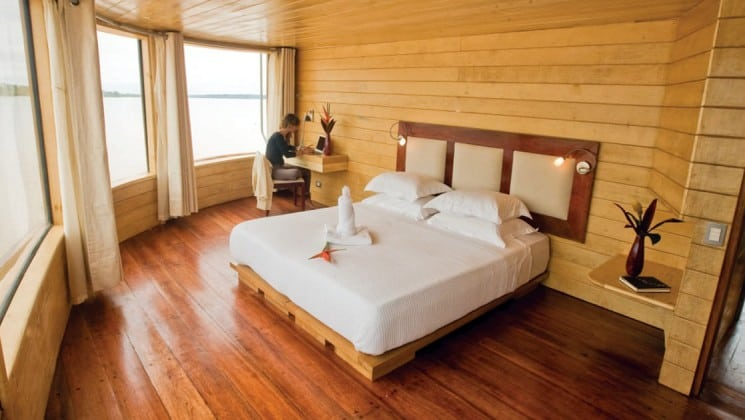 Woman writes at corner desk in Master Suite with large bed and picture windows aboard Delfin II riverboat on Amazon River cruise