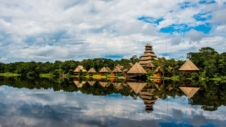 The triangular buildings of the Napo Wildlife Center reflect in the calm water of Anangucocha Lake. The sustainable eco lodge is surrounded by a 53,000 acre rainforest biosphere reserve within Yasuni National Park, offers luxury accommodations in Ecuador's Amazon.