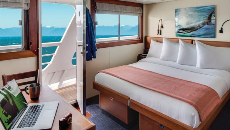 Large bed, desk, chair, large windows and door opening to outside aboard National Geographic Sea Bird expedition ship