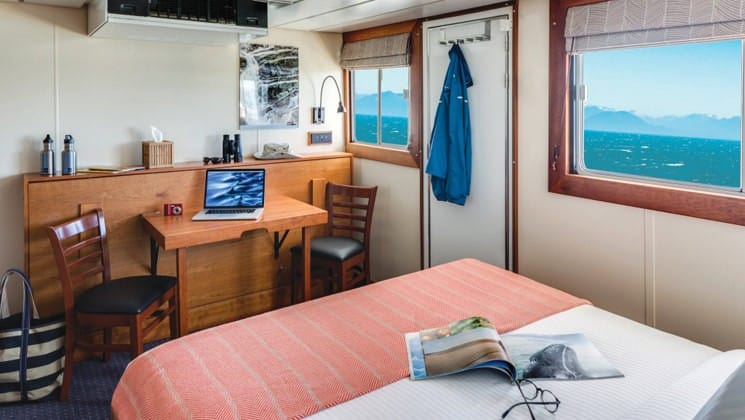 Category 3 cabin with large bed, table, two chairs, two windows and door to outside National Geographic Sea Bird expedition ship