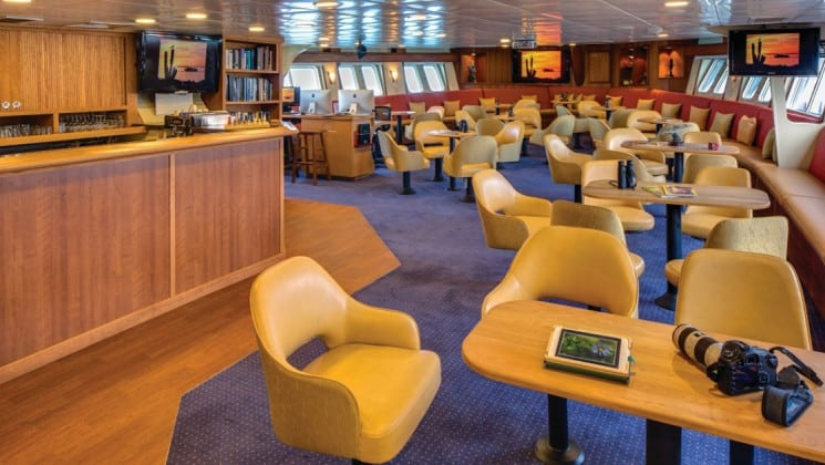 Tables and chairs near bar in window-lined lounge aboard National Geographic Sea Bird expedition ship