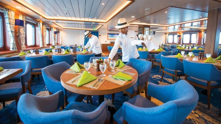 Crew members set the tables in the dining room awash with natural light aboard National Geographic Endeavour II expedition ship in the Galapagos Islands