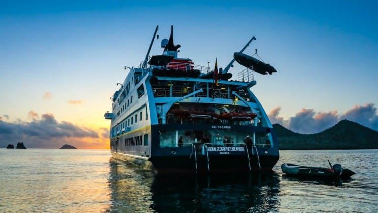 Full view of the stern of National Geographic Endeavour II expedition ship at sunset in the Galapagos Islands, with crew loading boats used for shore excursions