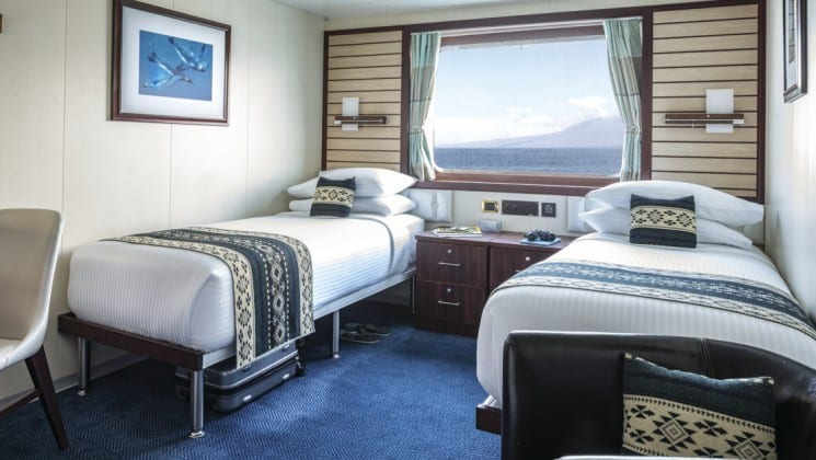 Two beds, bedside table, two chairs and large window in Category 4 cabin aboard National Geographic Endeavour II expedition ship in the Galapagos Islands