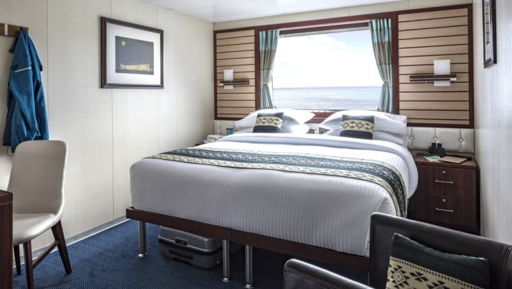 Category 4 cabin interior with large bed, armchair, bedside tables, desk, chair and window aboard National Geographic Endeavour II expedition ship in the Galapagos Islands