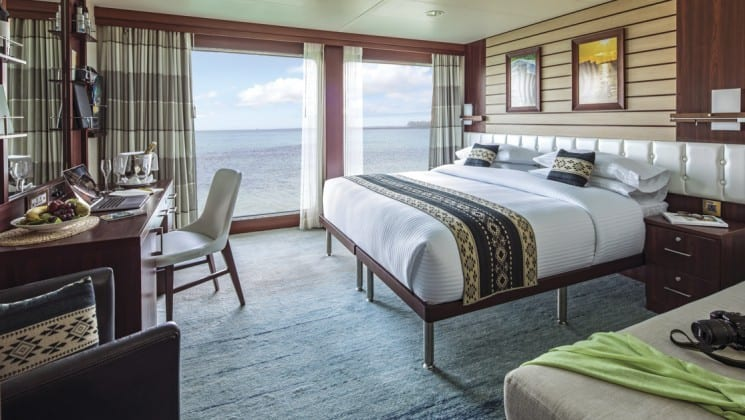 Interior of Suite B with large bed, couch, armchair, desk, chair and floor-to-ceiling windows aboard National Geographic Endeavour II expedition ship in the Galapagos Islands