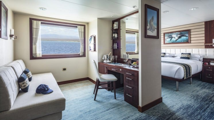 Suite C interior with large bed, couch, desk, chair and large windows aboard National Geographic Endeavour II expedition ship in the Galapagos Islands