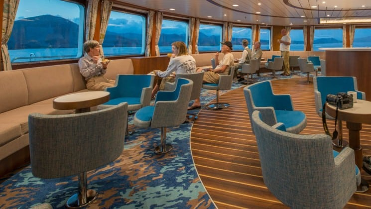 Passengers sit at couches and tables beneath large windows in the lounge aboard National Geographic Endeavour II expedition ship in the Galapagos Islands