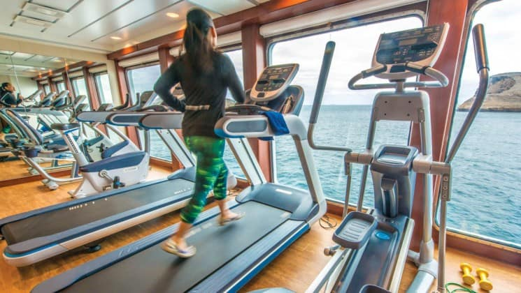 Woman running on treadmill among several exercise machines facing floor-to-ceiling windows in gym aboard National Geographic Endeavour II expedition ship in the Galapagos Islands