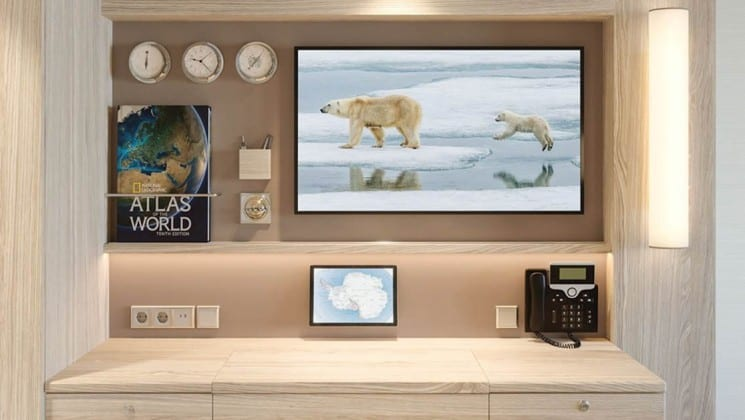 Rendering of cabin desk with TV, atlas, phone, and clocks aboard National Geographic Endurance & Resolution polar expedition ships