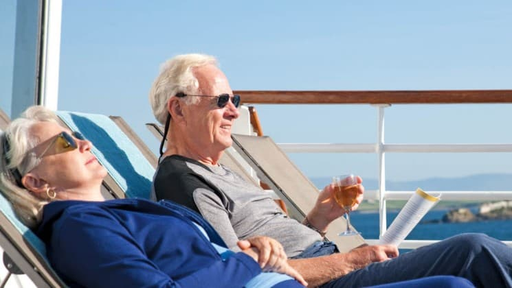 Woman and man relax in lounge chairs on Back Deck aboard National Geographic Explorer polar expedition ship