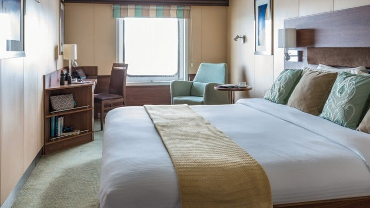 Large bed, desk, chairs and large window in Category 3 cabin aboard National Geographic Explorer polar expedition ship