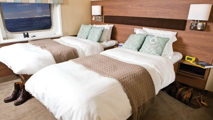 Two beds, nightstands and large window in Category 4 cabin aboard National Geographic Explorer polar expedition ship
