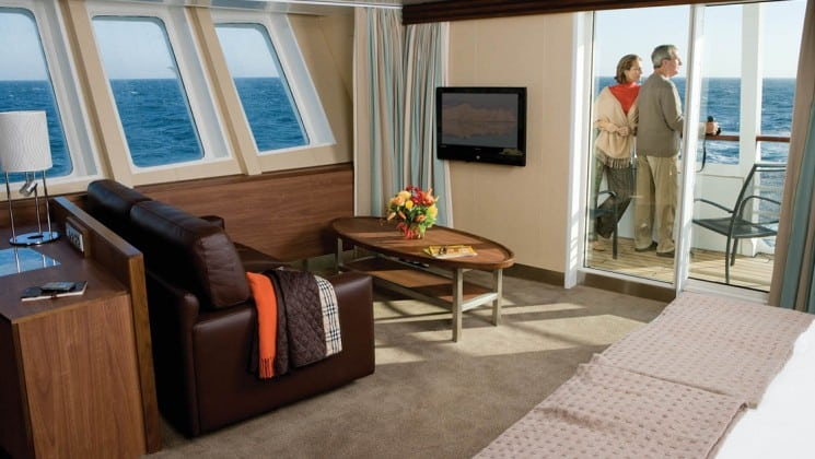 Man and woman standing on private balcony of Category 7 suite with large bed, desk, couch, coffee table, TV and several windows aboard National Geographic Explorer polar expedition ship