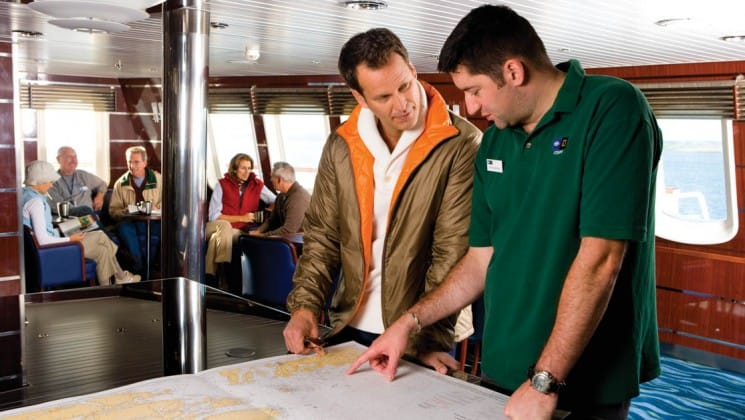 Crew member shows passenger details on map in the Chart Room aboard National Geographic Explorer polar expedition ship