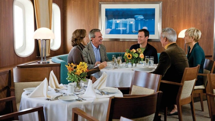 Five guests sit at a corner table beneath large windows in Dining Room aboard National Geographic Explorer polar expedition ship