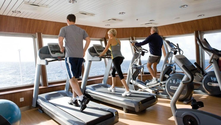 Guests use treadmills and elliptical machines in front of floor-to-ceiling windows in Fitness Center aboard National Geographic Explorer polar expedition ship