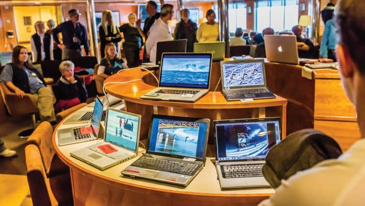Laptops set up on a table in a busy common area aboard National Geographic Explorer polar expedition ship