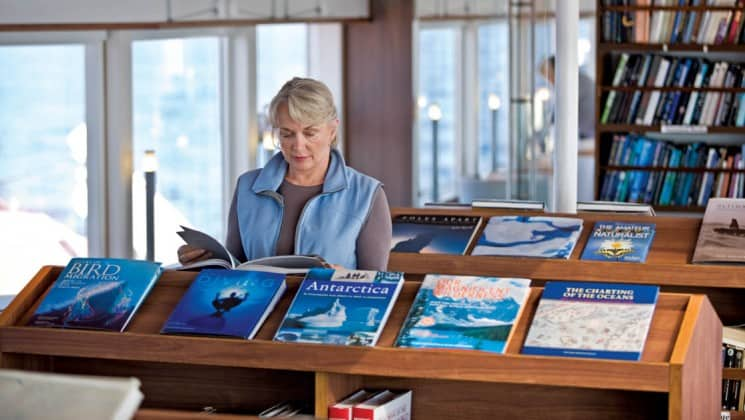 Woman exploring books beside large windows in library aboard National Geographic Explorer polar expedition ship