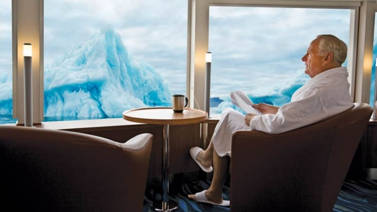 Man in bathroom reads paper in leather armchair beside large windows with views of glaciers aboard National Geographic Explorer polar expedition ship