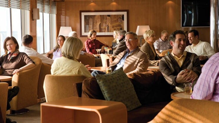 Guests sit on couches and comfortable chairs beside tables in the well-lit lounge aboard National Geographic Explorer polar expedition ship