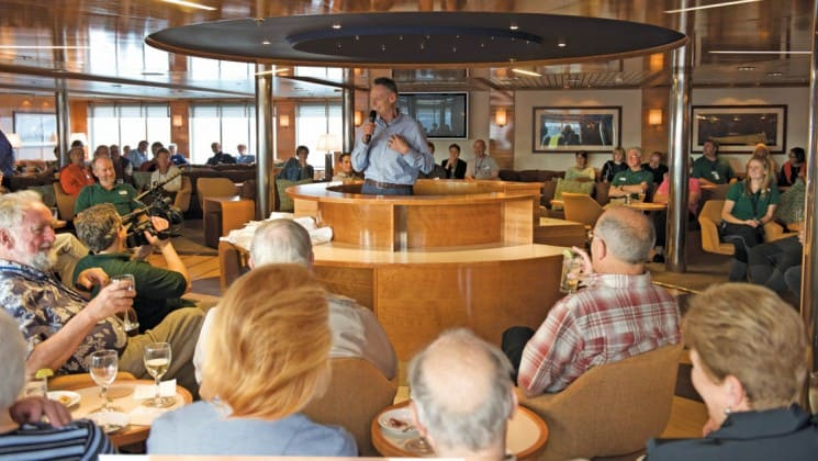 Guests sit on couches and chairs in lounge where man with microphone speaks in middle of room aboard National Geographic Explorer polar expedition ship