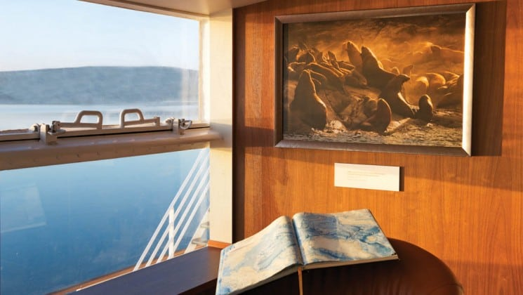 Ocean exhibit with sea lion photo and book in library aboard National Geographic Explorer polar expedition ship