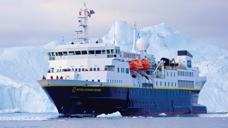 Full view of port side and bow of National Geographic Explorer polar expedition ship, with glaciers in the background