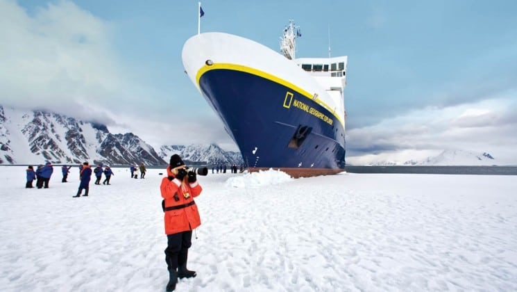 National Geographic Explorer polar expedition ship parked on a glacier with passengers disembarked