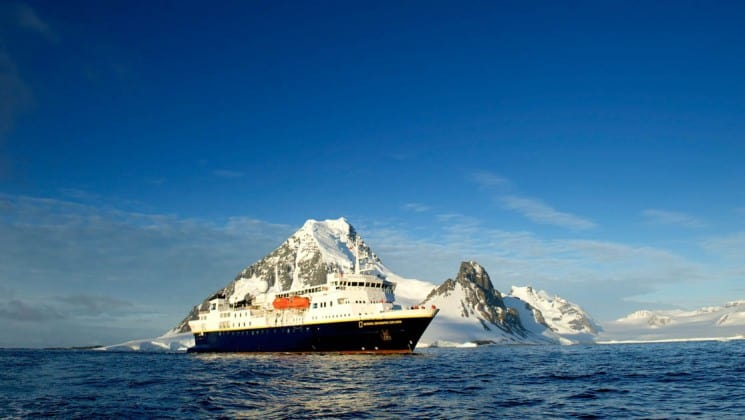 Full exterior of National Geographic Explorer polar expedition ship's starboard side near glacier