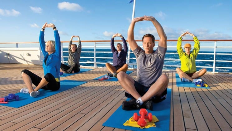 Five guests perform the same yoga pose on the Sun Deck aboard National Geographic Explorer polar expedition ship