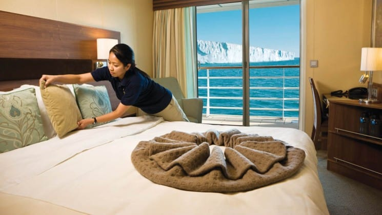 Crew member straightens pillows on large bed in Category 5 cabin with desk, chair and private balcony aboard National Geographic Explorer polar expedition ship