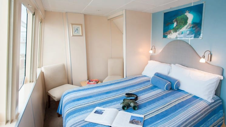 large bed with striped cover next to windows aboard the panama discovery small ship