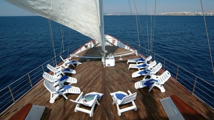 bow of the Panorama Mediterranean luxury yacht with chairs around the sail on a sunny day