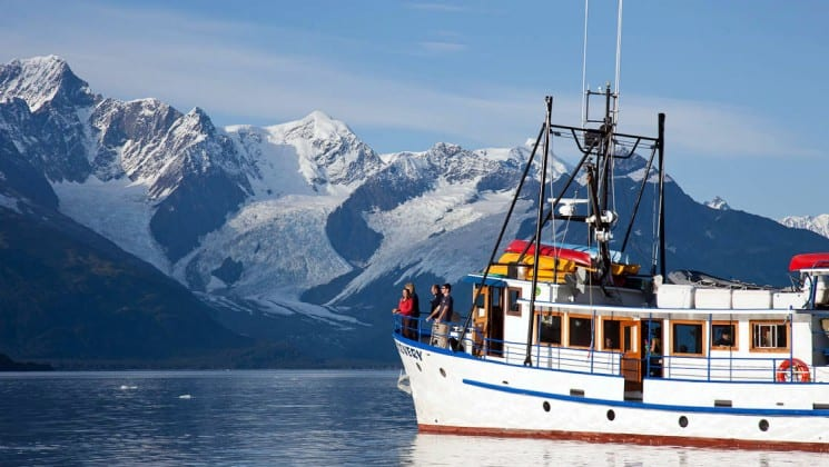 Four people at the port bow aboard Discovery yacht in Alaska, as seen from nearby kayak