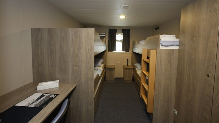 room with 4 beds and a window aboard Plancius Antarctica small ship