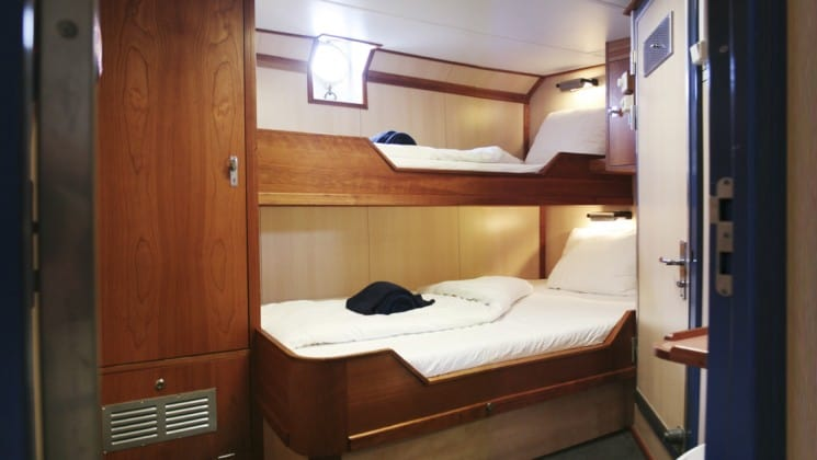 twin beds with a porthole on the wall in the cabin of the Rembrandt van Rijn arctic small ship
