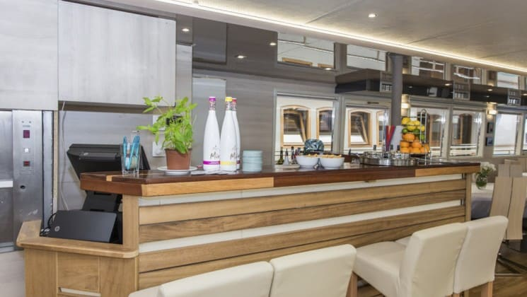 Riva Croatia luxury ship bar with wooden front, white bar stools and neutral accents throughout