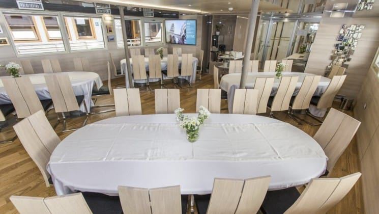 Riva Croatia small ship dining room with white tables and chairs and wood floors