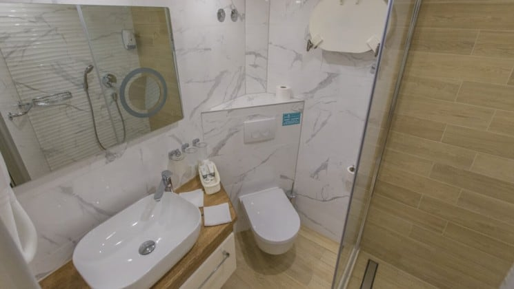 Riva Croatia small ship bathroom with marble walls, a mirror, toilet and sink