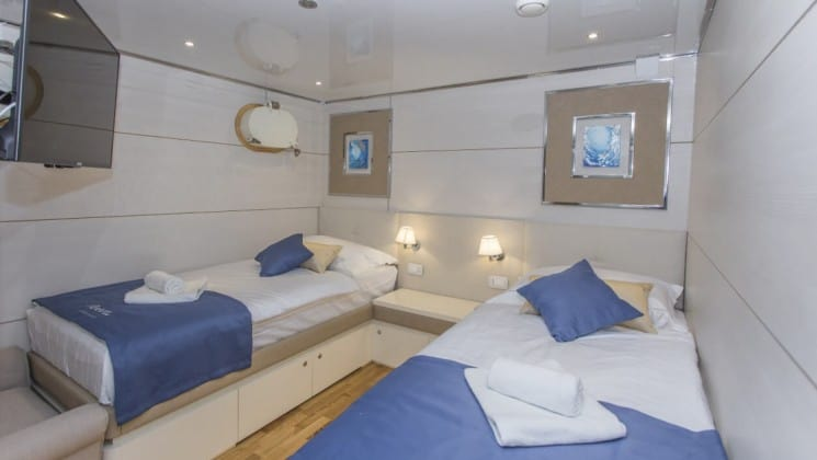 Riva Croatia small ship lower deck cabin with 2 beds, pictures on the wall, a porthole and blue and wood accents